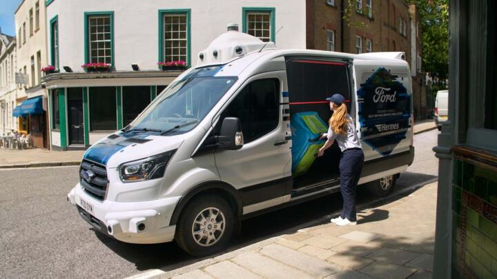 """Field testing of self-driving technology. In the UK, automaker Ford and delivery service Hermes are investigating how other road users behave when encountering a seemingly driverless van that's equipped with all the typical sensors of a fully autonomous vehicle. The idea behind it is that the driver in the field has a range of tasks such as sorting, loading and handing out parcels besides operating the vehicle. In this test, the """"invisible"""" driver remained totally passive. Couriers called the delivery vehicle via an app, and voice messages and monitors guided them to the parcel box intended for them."""