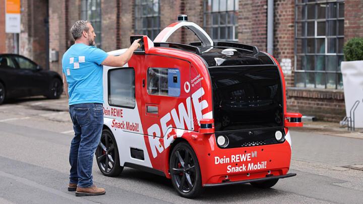 <br/>Ein rollender Automat bis vor die Tür. Netzbetreiber Vodafone und Lebensmittel-Einzelhändler Rewe testen aktuell ein selbstfahrendes Projektfahrzeug, das Snacks und Getränke ausliefert. Das Snack-Mobil rollt in einer Dauerschleife mit 6 km/h über einen Gewerbecampus in Köln. Um das Fahrzeug zum Stoppen zu bringen, reicht es aus, kurz zu winken. Kameras und Sensoren auf dem Dach erkennen die Handzeichen. Ein echter Vorgeschmack auf den vernetzten Straßenverkehr der Zukunft.