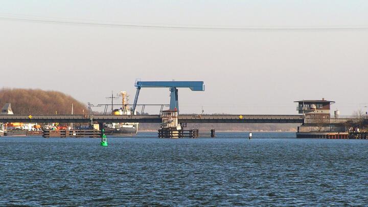 <strong>Rügen (D)</strong><br/>Die Ziegelgraben-Zugbrücke für Straßen- und Schienenverkehr verbindet die Insel Rügen mit dem Festland. Sie besteht aus drei Teilen: zwei festen Brücken mit je 52 Meter Stützweite und dem klappbaren Mittelteil (29 Meter). FAG hatte schon den Vorgänger aus dem Jahr 1937 mit Pendelrollenlagern ausgerüstet. Beim Umbau in den 1990er-Jahren wurden in allen Drehpunkten (Klappe, Waagebalken, Zugstangen) Elgoglide-beschichtete Gelenklager verbaut.